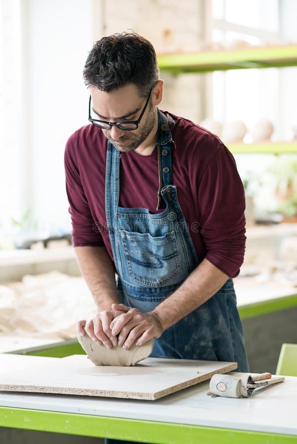Iklädd Ceramist ett förkläde som arbetar med rå lera i ljust keramiskt seminarium arkivfoto