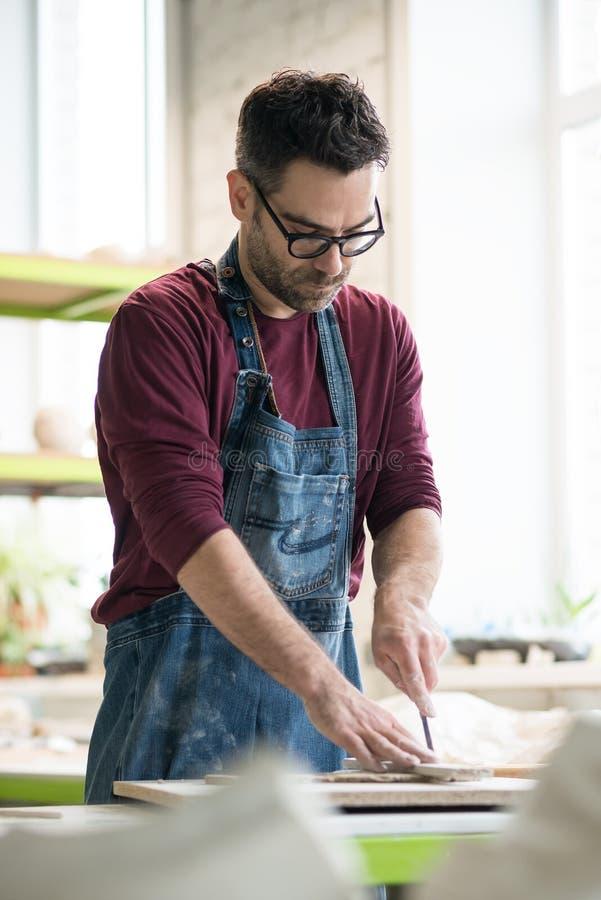 Iklädd Ceramist ett förkläde som arbetar med rå lera i ljust keramiskt seminarium royaltyfri bild