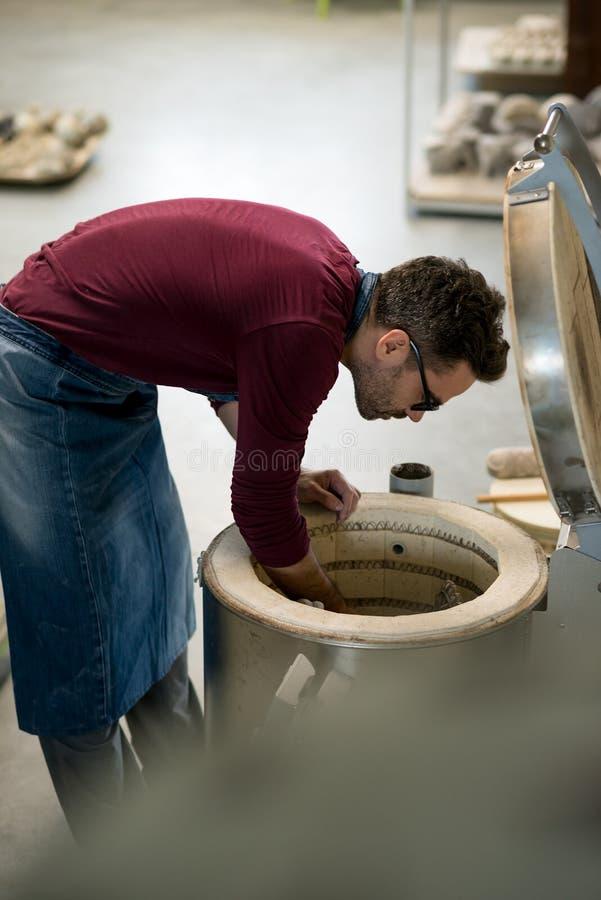 Iklädd Ceramist ett förkläde som förlägger Clay Sculpture i elektrisk ugn royaltyfria bilder