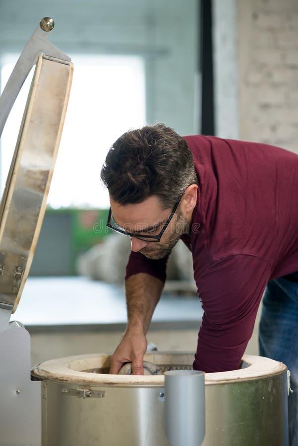 Iklädd Ceramist ett förkläde som förlägger Clay Sculpture i elektrisk ugn royaltyfria foton