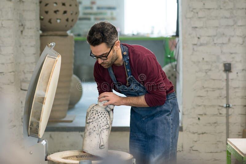 Iklädd Ceramist ett förkläde som förlägger Clay Sculpture i elektrisk ugn royaltyfri foto