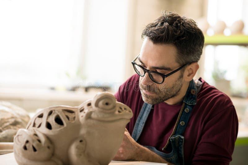 Iklädd Ceramist ett förkläde som hugger statyn från rå lera i ljust keramiskt seminarium arkivfoton
