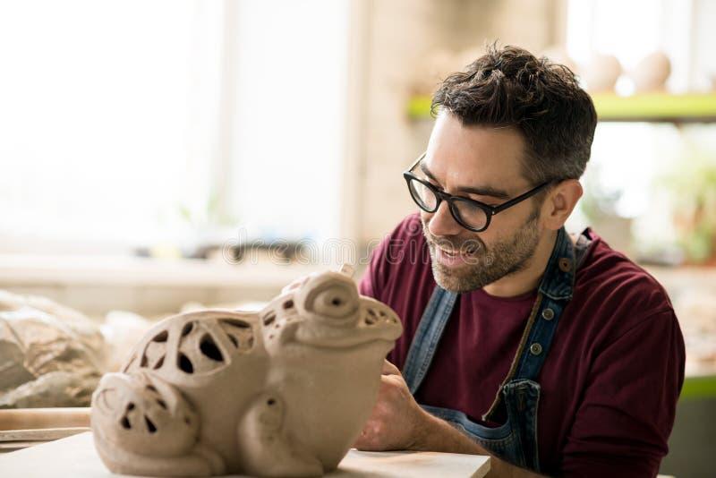 Iklädd Ceramist ett förkläde som hugger statyn från rå lera i ljust keramiskt seminarium arkivbild