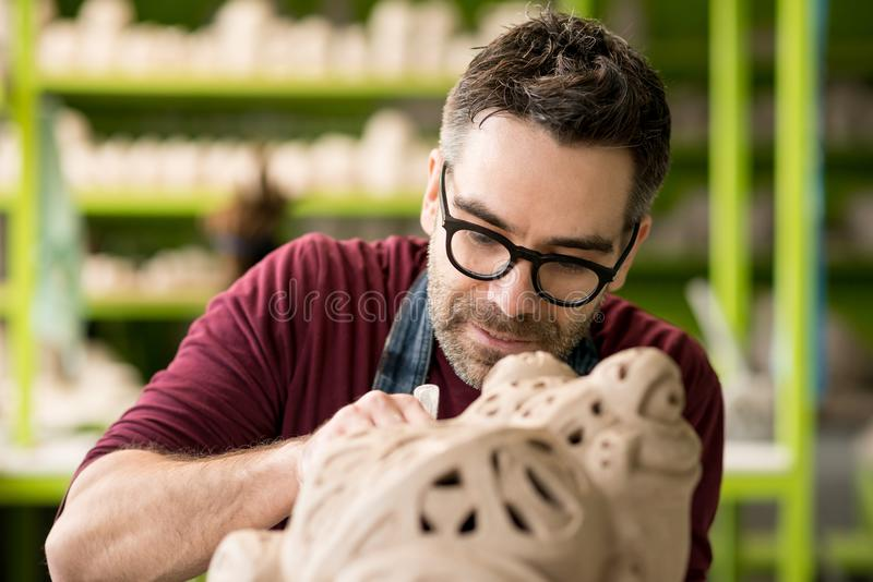 Iklädd Ceramist ett förkläde som hugger statyn från rå lera i ljust keramiskt seminarium arkivbilder
