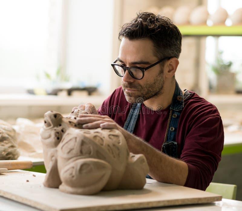 Iklädd Ceramist ett förkläde som hugger statyn från rå lera i ljust keramiskt seminarium royaltyfri foto