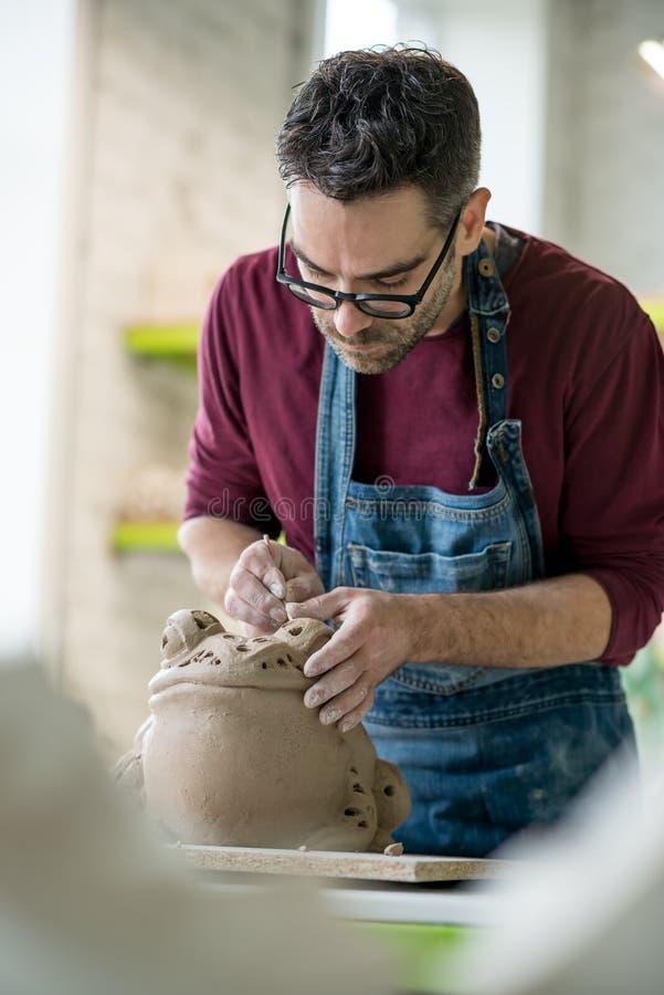 Iklädd Ceramist ett förkläde som hugger statyn från rå lera i ljust keramiskt seminarium royaltyfria bilder