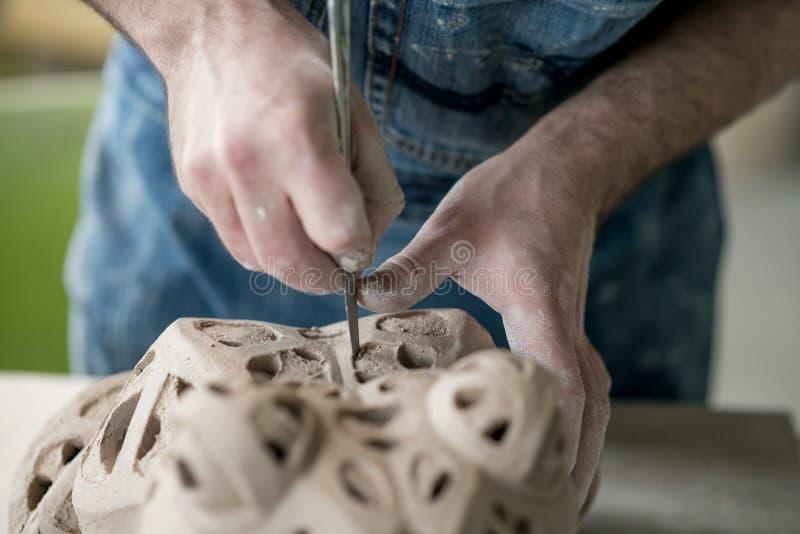 Iklädd Ceramist ett förkläde som hugger statyn från rå lera i ljust keramiskt seminarium royaltyfria foton