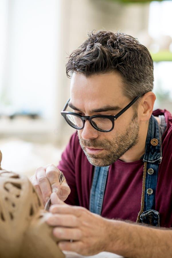 Iklädd Ceramist ett förkläde som hugger statyn från rå lera i ljust keramiskt seminarium fotografering för bildbyråer
