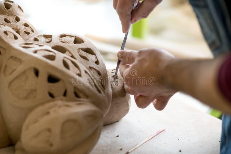 Iklädd Ceramist ett förkläde som hugger statyn från rå lera i ljust keramiskt seminarium arkivfoto