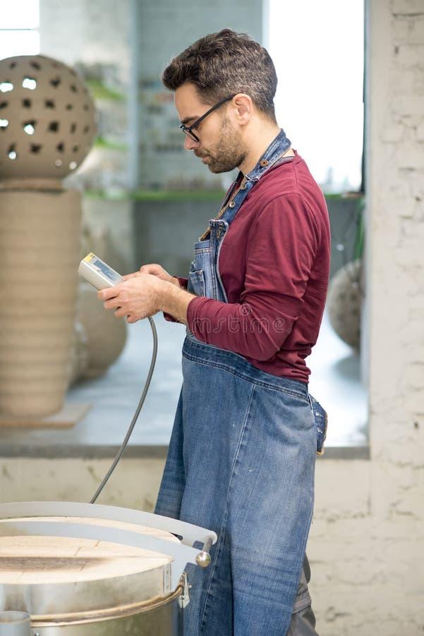 Iklädd Ceramist ett förkläde som ställer in den elektriska ugnen för att torka Clay Sculpture Using Control Console arkivfoton