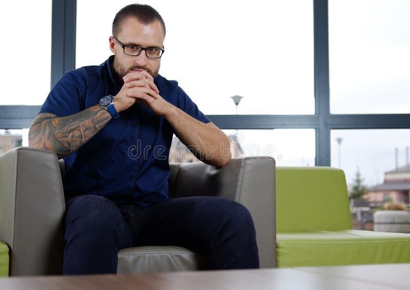 Iklädd eftertänksam affärsman en blå skjorta som sitter på soffan i kontoret arkivfoto
