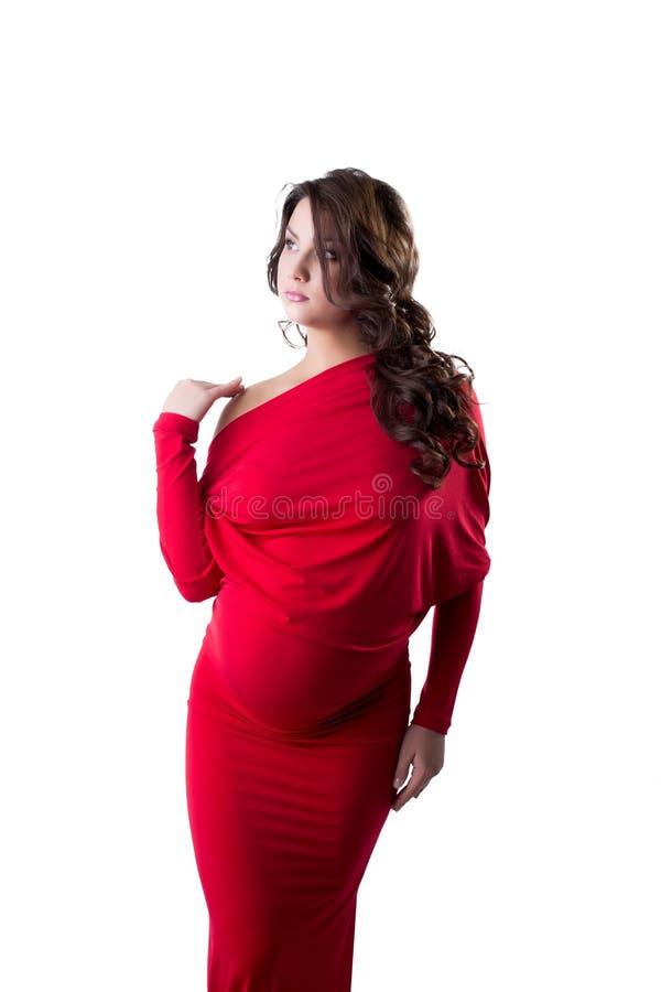 Iklädd elegant klänning för eftertänksam gravid kvinna arkivbild