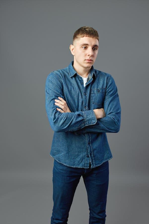 Iklädd grabb en vit t-skjorta, jeans och jeansskjorta som står med hans armar vikta i studion på den gråa bakgrunden arkivfoton