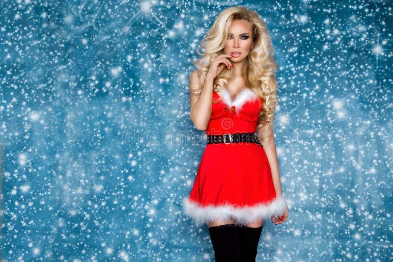 Iklädd härlig sexig blond kvinnlig modell en Santa Claus hatt och klänning Sinnlig flicka för jul royaltyfri foto
