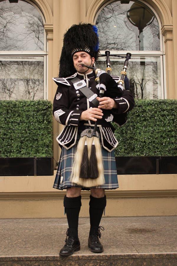 Iklädd kilt för säckpipe- spelare som spelar på framdel av Hilton Hotel i Glasgow, Skottland royaltyfri fotografi