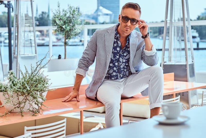 Iklädd modern elegant kläder för lyckad stilfull man som sitter på tabellen på det utomhus- kafét mot bakgrunden av staden arkivfoton