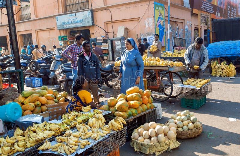 Iklädd nunna för kvinna av katolska melon och bananer för en beställningsköpande på grönsakmarknad av staden arkivfoto