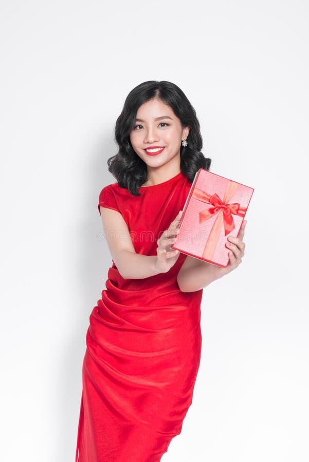 Iklädd röd klänning för nätt ung glamorös asiatisk kvinna med ett p arkivbild