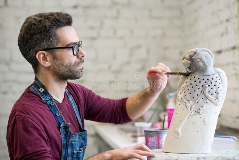 Iklädd stående av ceramisten ett förkläde som arbetar på Clay Sculpture i ljust keramiskt seminarium royaltyfri bild
