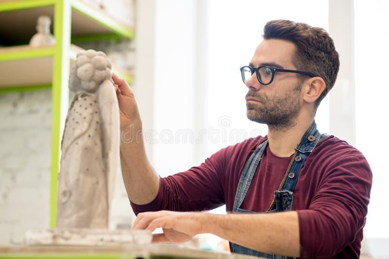 Iklädd stående av ceramisten ett förkläde som arbetar på Clay Sculpture i ljust keramiskt seminarium royaltyfri foto