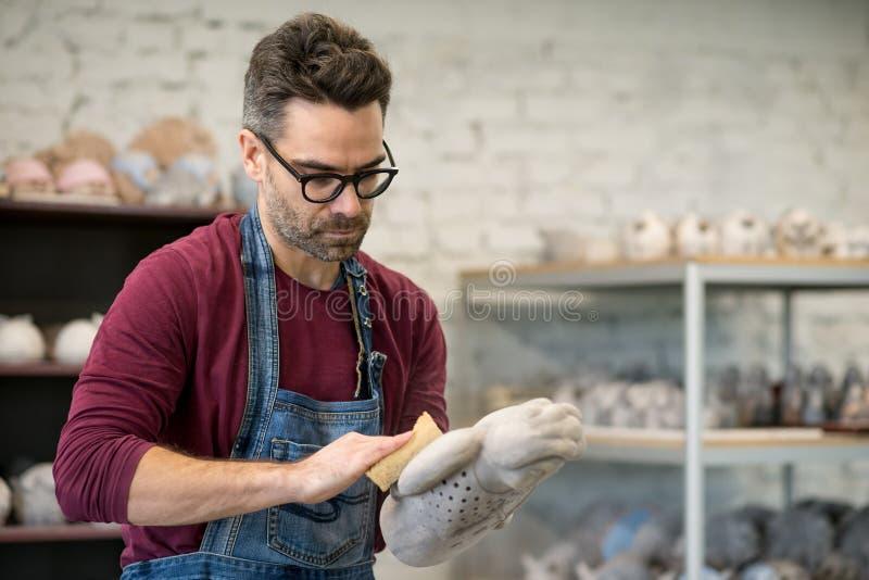 Iklädd stående av ceramisten ett förkläde som arbetar på Clay Sculpture i ljust keramiskt seminarium arkivbild