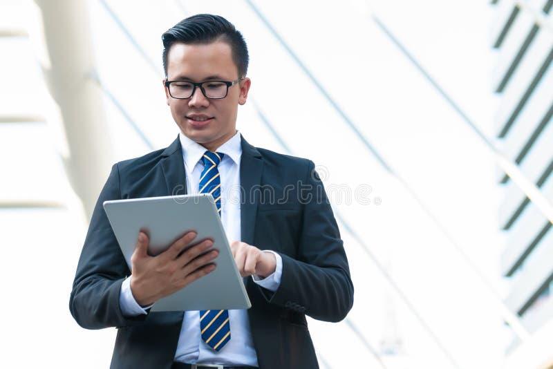 Iklädd svart dräkt för lycklig affärsman utanför kontor och leende Begrepp f?r Digital teknologi royaltyfria bilder