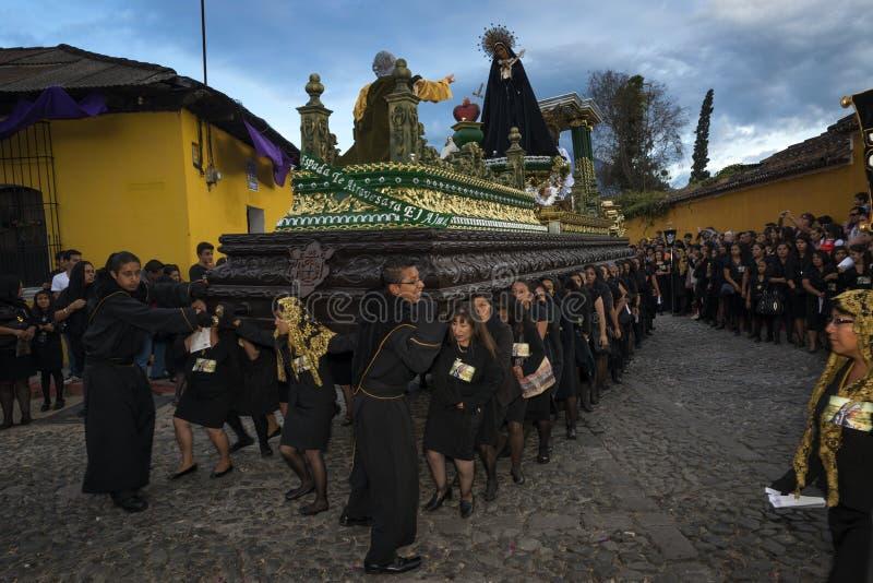 Iklädd svart för kvinnor som bär en jätte- flöte i en gata av den gamla staden av Antigua under en procession av den heliga vecka arkivfoto