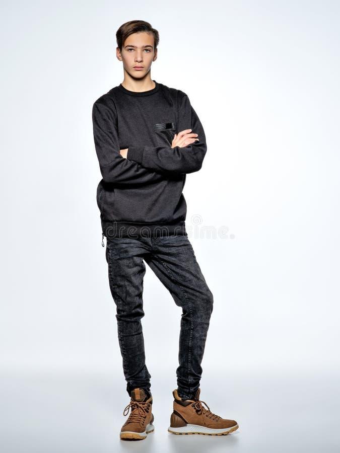 Iklädd svart moderiktig kläder för tonårs- pojke som poserar på studion fotografering för bildbyråer