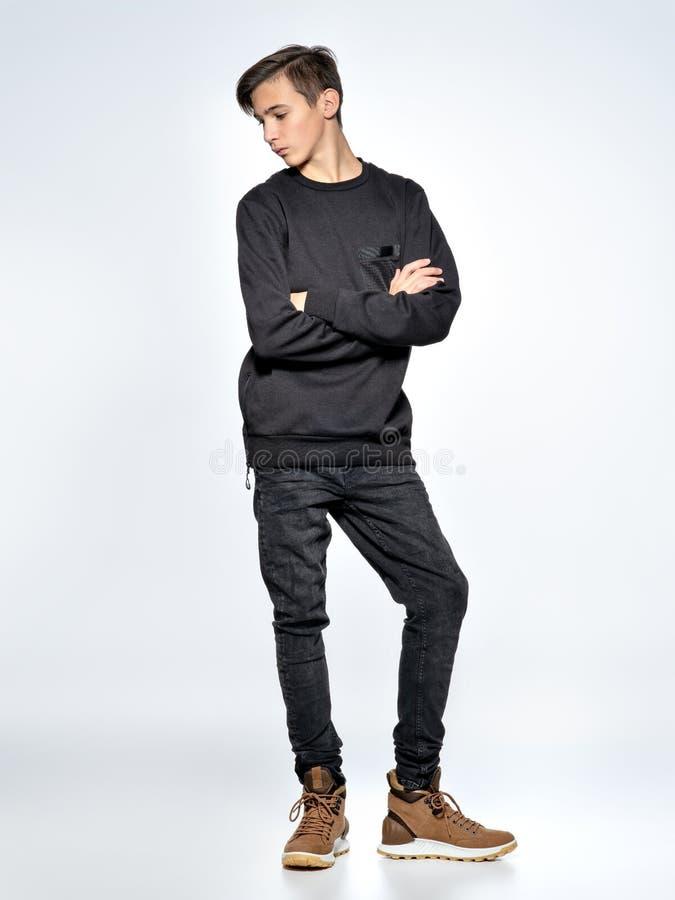 Iklädd svart moderiktig kläder för tonårs- pojke som poserar på studion royaltyfri fotografi