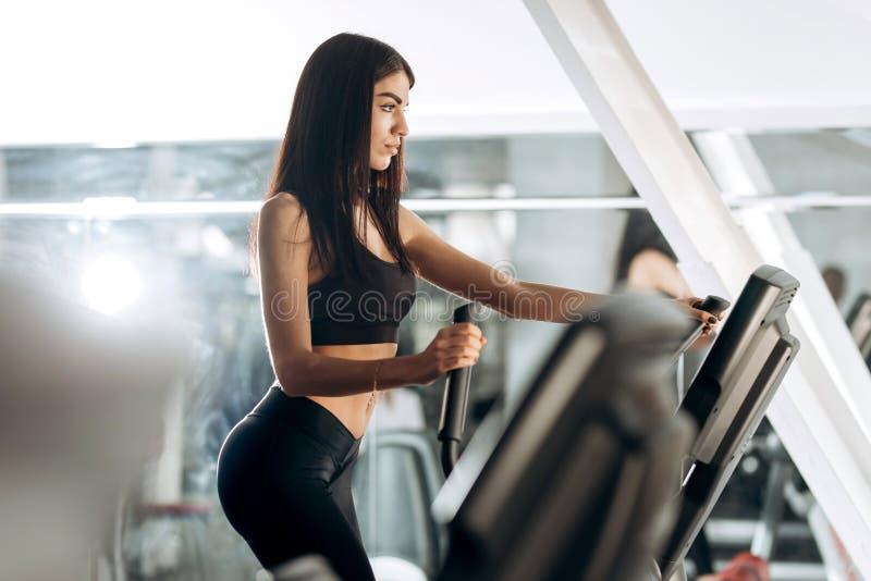 Iklädd svart sportswear för slank mörker-haired flicka att utarbeta på en trampkvarn i idrottshallen arkivfoton