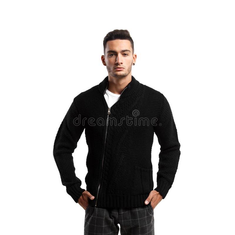 Iklädd svart tröja för ung man med en blixtlås och gråa ställningar för plädflåsanden på den vita bakgrunden royaltyfri foto