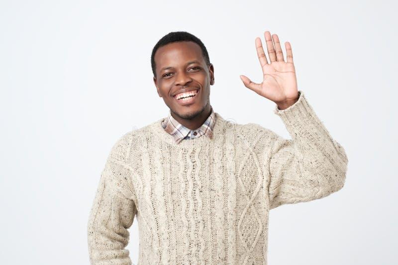 iklädd sweatersaying för ung afrikansk amerikanman hi och att vinka hans hand royaltyfria foton