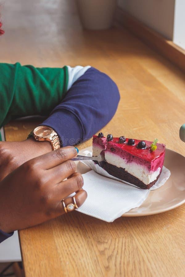 Iklädd tillfällig kläder för ung mörkhyad kvinna som rymmer koppen av den varma drinken och att tycka om kaffe eller te fotografering för bildbyråer