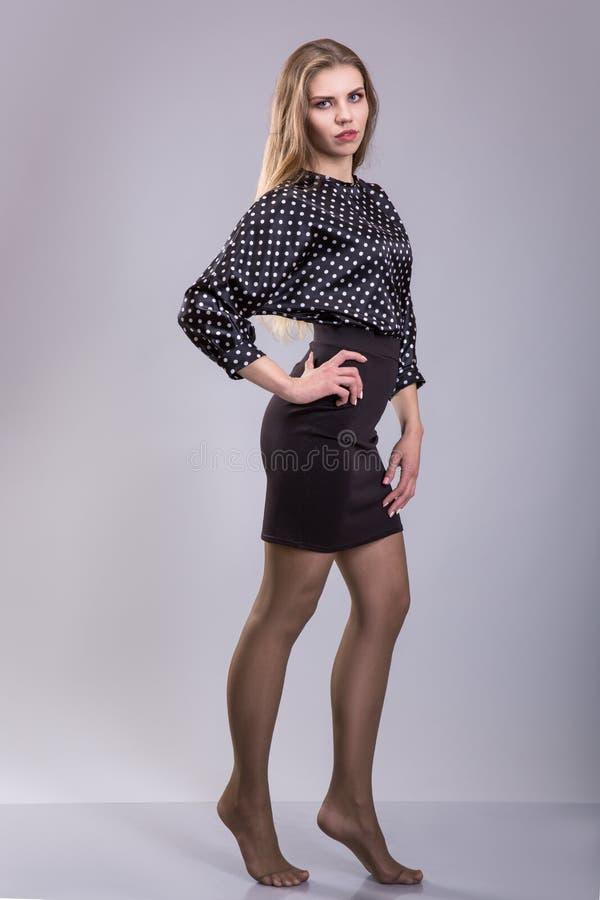 Iklädd trendig kvinna en blus för prickar som står på den gråa bakgrunden fotografering för bildbyråer