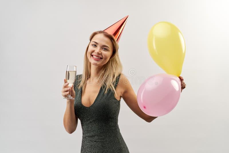 Iklädd ung attraktiv le flicka en klänning med ett exponeringsglas av arkivfoton