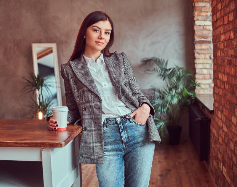 Iklädd ung kvinna en grå elegant omslagsinnehavkopp av takeaway kaffe, medan luta på en tabell i ett rum med vinden fotografering för bildbyråer