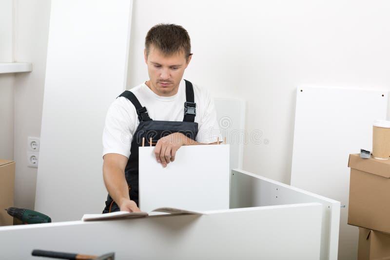 Iklädda arbetare för man som assembing överallt möblemang fotografering för bildbyråer
