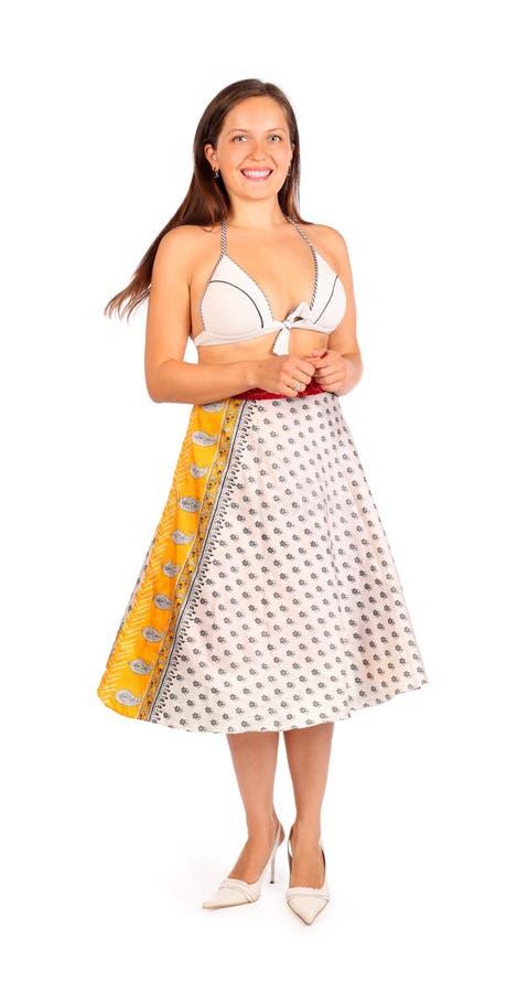 Iklädda bikini- och skirtleenden för härlig kvinna arkivbild