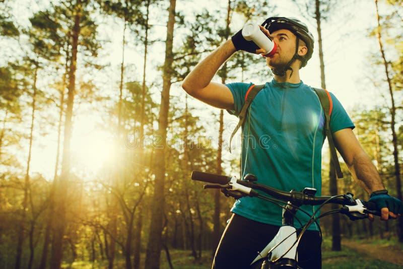 Iklädda cykla kläder för stilig ung yrkesmässig cyklist och skyddande hjälm som känner sig fria och lyckliga, dricksvatten från arkivbilder