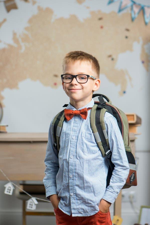 Iklädda exponeringsglas för skolpojke och ett ryggsäckanseende i klassrumet arkivbilder