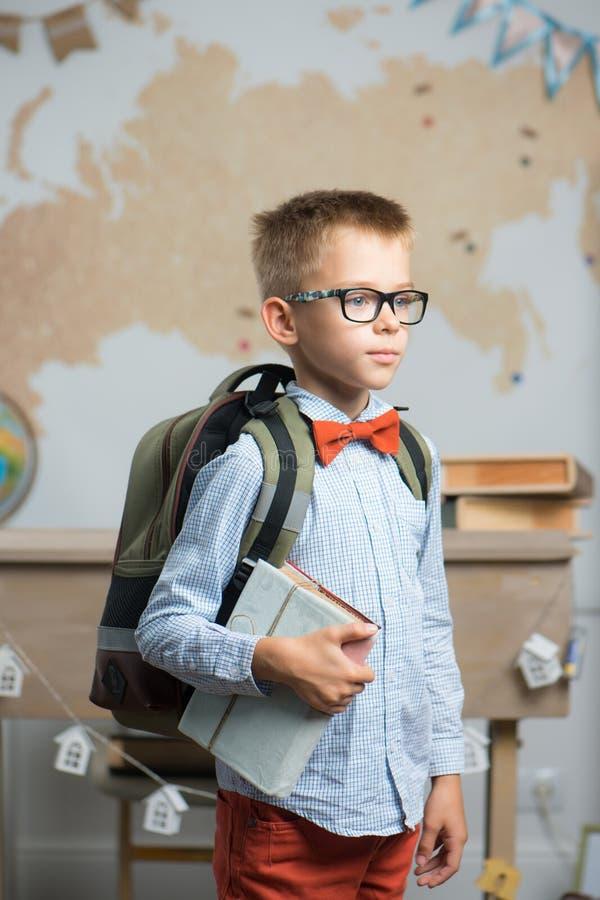 Iklädda exponeringsglas för skolpojke och ett ryggsäckanseende i klassrumet royaltyfri foto