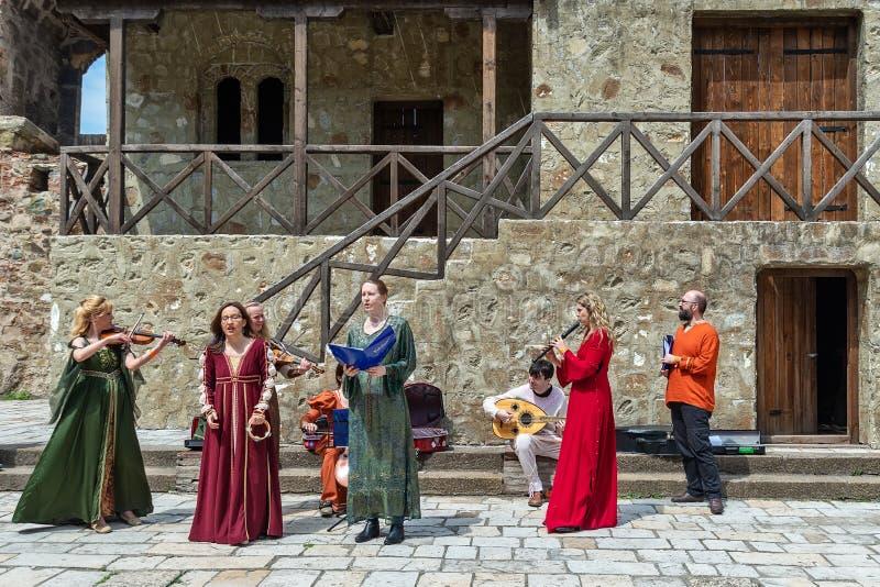 Iklädda medeltida dräkter för konstnärer och spelamusik från medeltiden arkivbilder