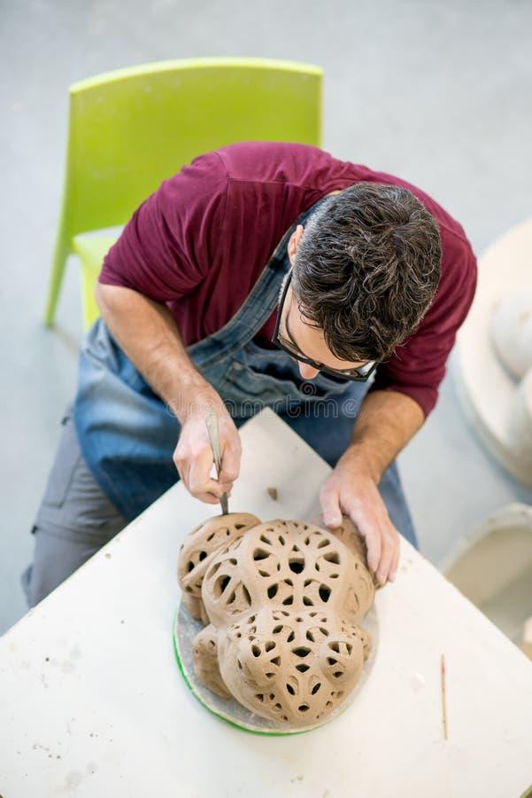 Iklädda Topview av ceramisten ett förkläde som hugger statyn från rå lera i ljust keramiskt seminarium royaltyfri foto