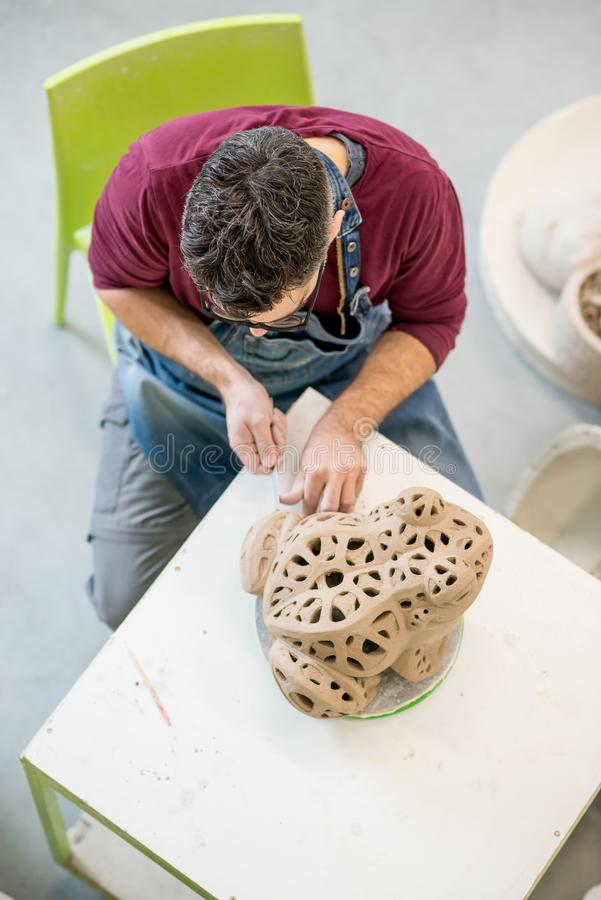Iklädda Topview av ceramisten ett förkläde som hugger statyn från rå lera i ljust keramiskt seminarium royaltyfri fotografi
