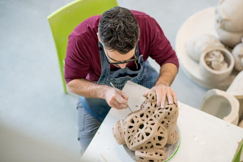 Iklädda Topview av ceramisten ett förkläde som hugger statyn från rå lera i ljust keramiskt seminarium royaltyfria foton