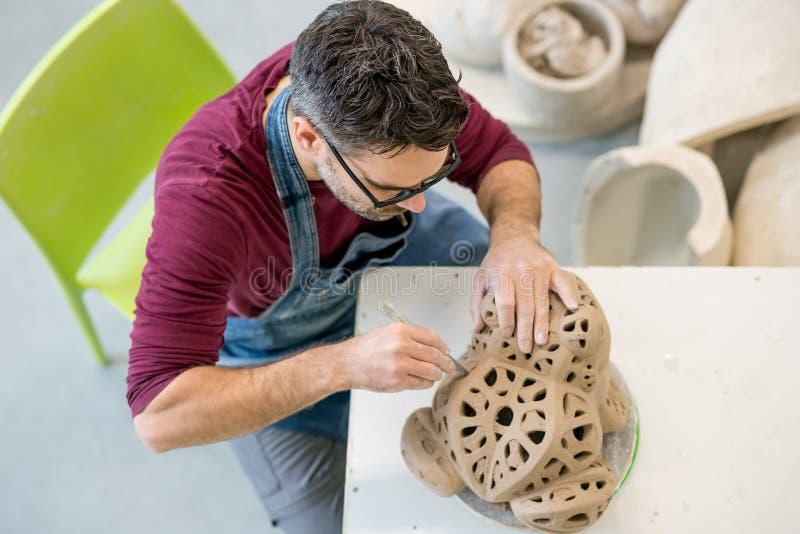 Iklädda Topview av ceramisten ett förkläde som hugger statyn från rå lera i ljust keramiskt seminarium fotografering för bildbyråer