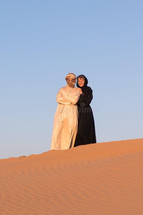 Iklädda traditionella arabiska kläder för par i öken arkivbilder