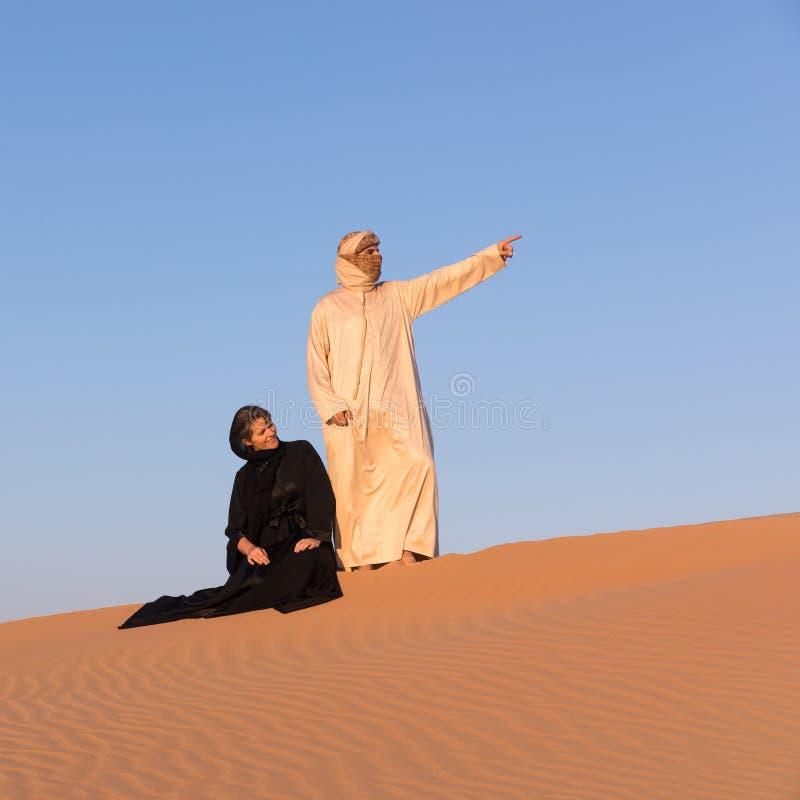 Iklädda traditionella arabiska kläder för par i öken royaltyfri foto