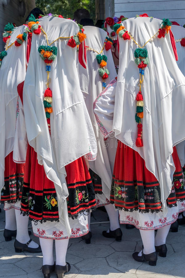 Iklädda traditionella folkdräkter för bulgariska flickor arkivfoto