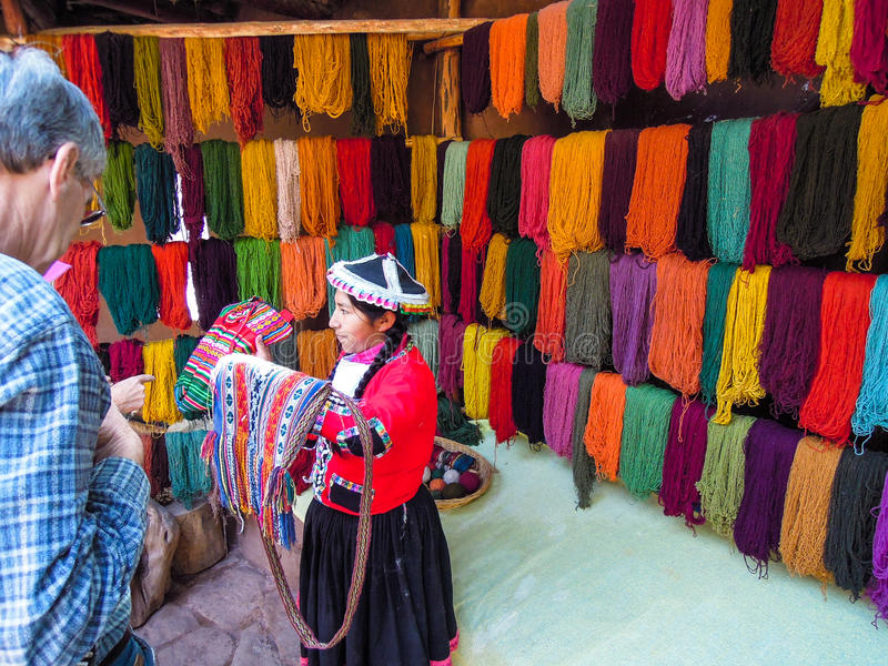Iklädda traditionella kläder för lokal kvinna framme av färgad alpacaull i Awana Kancha arkivfoto